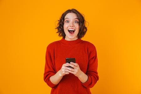 Portrait of caucasian woman 20s wearing sweater holding et à l'aide de téléphone portable tout en se tenant isolé sur fond jaune