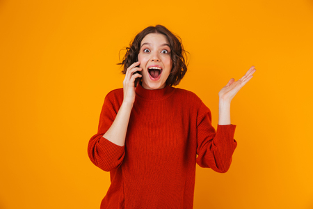 Portrait of positive woman 20s wearing sweater holding and speaking on cell phone while standing isolated over yellow background