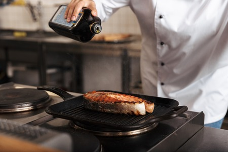 Smiling woman chef cook wearing uniform cooking delicious salmon steak standing at the kitchen, pouring olive oil