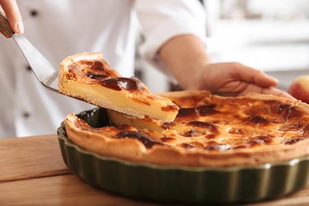Image d'une femme chef portant un uniforme blanc coupant une tarte aux pommes pendant la cuisson dans la cuisine de la boulangerie Banque d'images