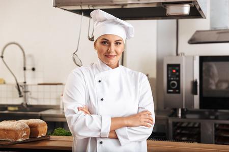 Portrait of beautiful woman chef wearing white uniform posing in kitchen at the restaurant Reklamní fotografie