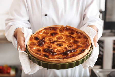 Image of young woman chef wearing white uniform holding apple pie while cooking in kitchen at the bakery