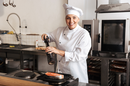 Smiling woman chef cook wearing uniform cooking delicious salmon steak standing at the kitchen Archivio Fotografico - 119441719