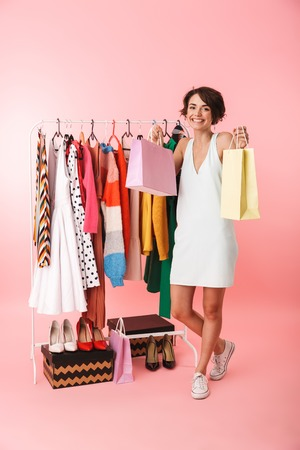 Image of a beautiful woman stylist posing isolated over pink wall background near a lot of clothes holding shopping bags.