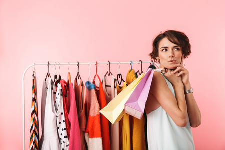 Image of a beautiful thoughtful woman stylist posing isolated over pink wall background near a lot of clothes holding shopping bags. Stock Photo