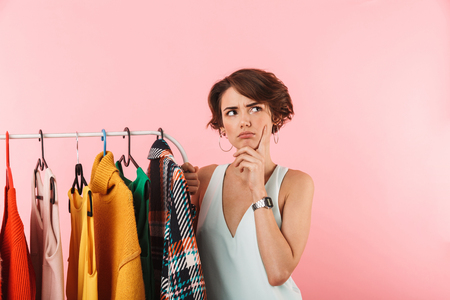 Image of a beautiful thoughtful woman stylist posing isolated over pink wall background near a lot of clothes.