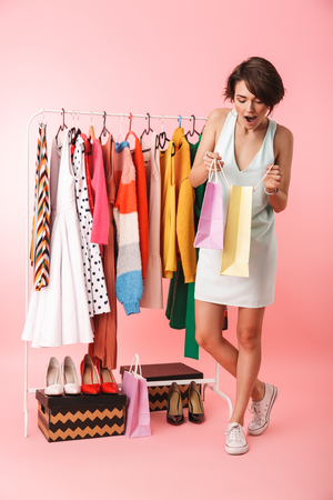 Image of a beautiful excited woman stylist posing isolated over pink wall background near a lot of clothes holding shopping bags. Stock Photo