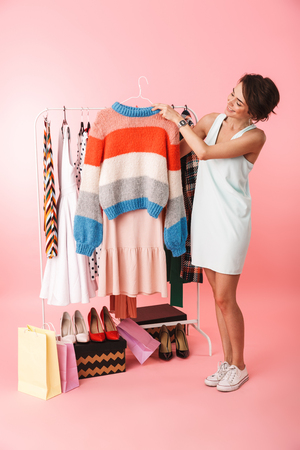 Image of a pretty woman stylist posing isolated over pink wall background near a lot of clothes.