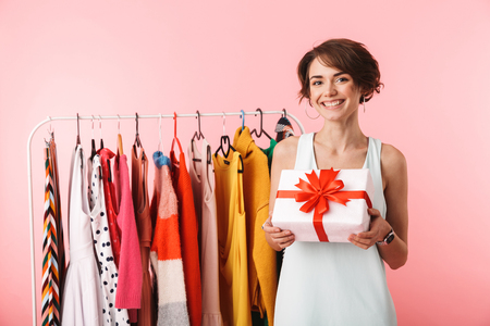 Beautiful young woman stylist standing at the clothes rack, holding present box