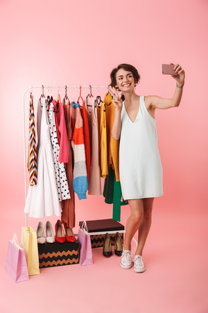 Image of a beautiful happy woman stylist posing isolated over pink wall background near a lot of clothes take a selfie by mobile phone.