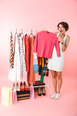 Beautiful young woman stylist standing at the clothes rack, picking clothes