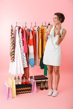 Image of a beautiful happy woman stylist posing isolated over pink wall background near a lot of clothes using mobile phone pointing.