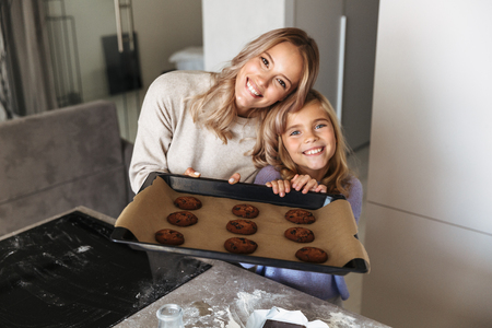 Image of a happy young woman with her little sister indoors at home kitchen cooking sweeties bakery.