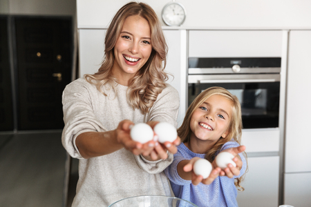 Image of a happy young woman with her little sister indoors at home kitchen cooking with flour and eggs.