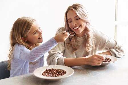 Image of two happy girls sisters at kitchen indoors eat have a breakfast together.