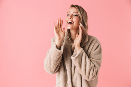 Image of a beautiful happy young pretty woman posing isolated over pink wall background screaming loud call out.