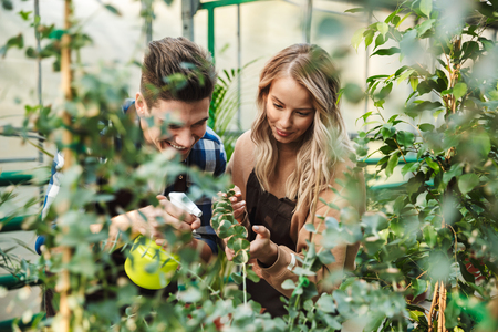 Image of two amazing gardeners posing in the nature greenhouse garden work with flowers plants.