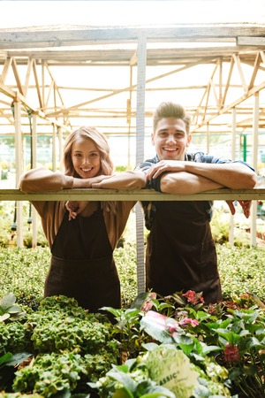 Image of two happy gardeners posing in the nature greenhouse garden.