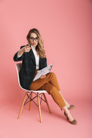 Portrait of european businesswoman 30s in stylish outfit holding paper documents with report while sitting on chair isolated over red background Stock Photo