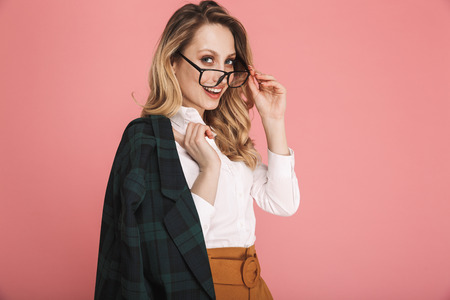 Portrait of gorgeous blond woman 30s in stylish outfit touching eyeglasses and looking on camera isolated over red background