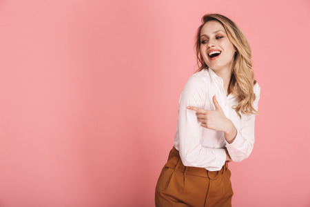 Portrait of glamour blond woman 30s in stylish outfit smiling and pointing finger at copyspace isolated over red background Stock Photo - 119564040