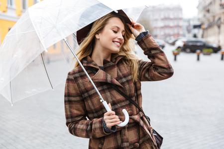 Beautiful young stylish blonde woman wearing a coat walking outdoors, holding umbrella