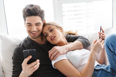 Portrait of attractive couple man and woman using mobile phones while lying on couch in bright room at home 写真素材 - 119916657