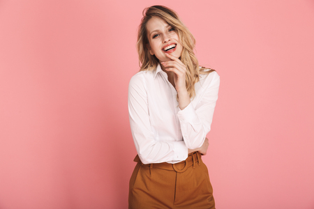Portrait of cheerful blond woman 30s in stylish outfit smiling and looking at camera isolated over red background Reklamní fotografie