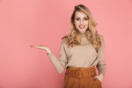 Portrait of adorable blond woman 30s in stylish outfit smiling and holding copyspace on palm isolated over red background
