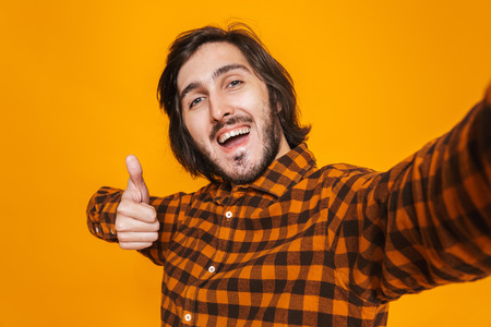 Portrait of smiling man wearing plaid shirt rejoicing and taking selfie photo while standing isolated over yellow background in studio Banco de Imagens