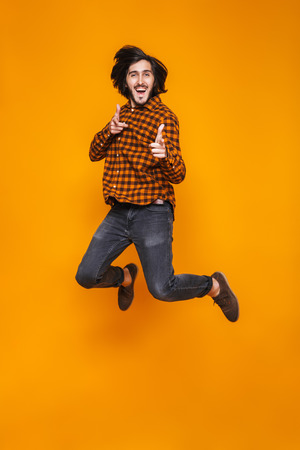 Full length portrait of hipster man 20s wearing plaid jumping and pointing fingers at you while standing isolated over yellow background in studio Stock Photo