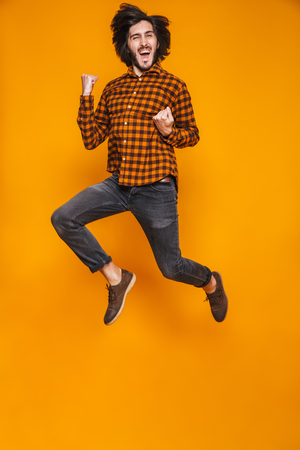 Full length portrait of positive man 20s wearing plaid jumping and clenching fists while standing isolated over yellow background in studio Stock Photo