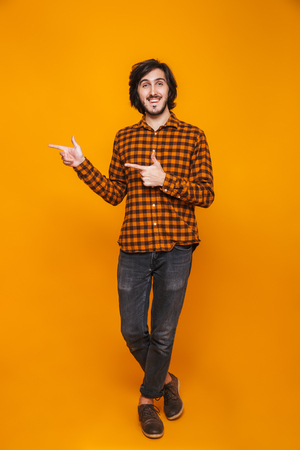 Full length portrait of cheerful man 20s wearing plaid smiling and pointing fingers aside while standing isolated over yellow background in studio