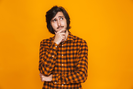 Portrait of thoughtful man wearing plaid shirt touching chin and looking upward while standing isolated over yellow background in studio