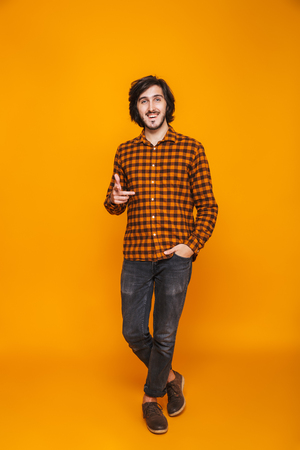 Full length portrait of happy man 20s wearing plaid smiling and pointing finger at you while standing isolated over yellow background in studio