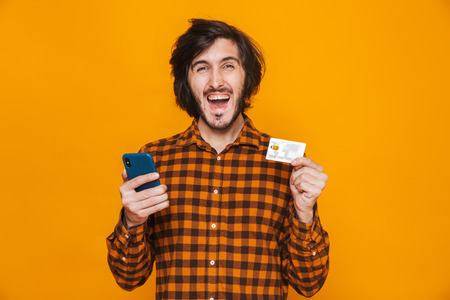 Photo of happy man wearing plaid shirt holding credit card and smartphone while standing isolated over yellow background in studio Reklamní fotografie