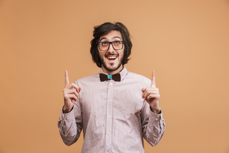 Portrait of optimistic man 20s wearing eyeglasses and bow tie pointing fingers upward at copyspace while standing isolated over beige background in studio Imagens - 119918847