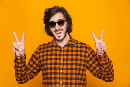 Portrait of trendy guy 20s wearing plaid shirt and sunglasses smiling and showing peace sign while standing isolated over yellow background in studio