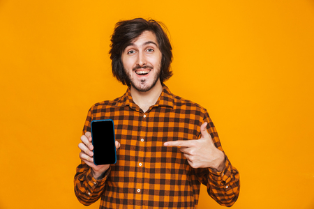 Photo of young man wearing plaid shirt laughing and using cell phone while standing isolated over yellow background in studio Stock Photo