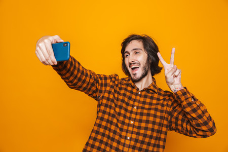 Photo of hairy man wearing plaid shirt having fun and taking selfie on cell phone while standing isolated over yellow background in studio Reklamní fotografie