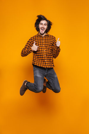 Full length portrait of attractive man 20s wearing plaid jumping and showing thumbs up while standing isolated over yellow background in studio