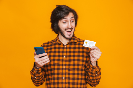 Photo of attractive man wearing plaid shirt holding credit card and smartphone while standing isolated over yellow background in studio 写真素材