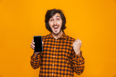 Photo of positive man wearing plaid shirt laughing and using cell phone while standing isolated over yellow background in studio Reklamní fotografie