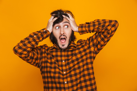 Portrait of nervous man grabbing head and shouting while standing isolated over yellow background in studio