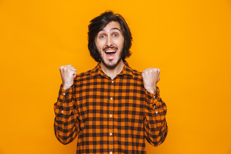 Portrait of happy man wearing plaid shirt rejoicing and clenching fists while standing isolated over yellow background in studio Imagens - 119919806