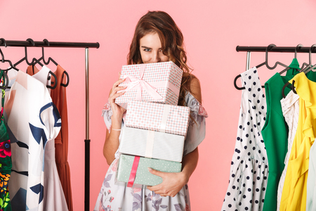 Photo of modest woman wearing dress standing in store near clothes rack with present boxes isolated over pink background 免版税图像