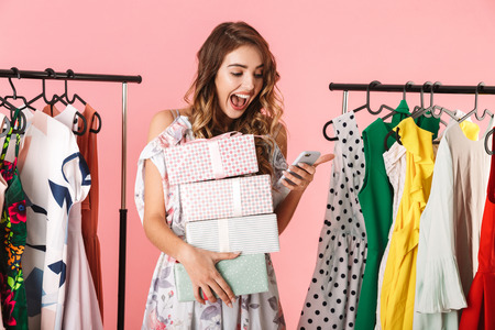 Photo of attractive woman with purchase standing in store near clothes rack and using mobile phone isolated over pink background