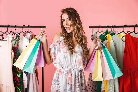 Photo of fashionable girl standing in store near clothes rack and holding colorful shopping bags isolated over pink background