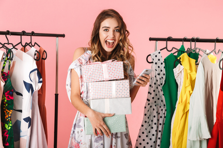 Photo of fashionable woman with purchase standing in store near clothes rack and using mobile phone isolated over pink background