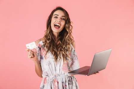 Photo of brunette woman 20s in dress holding silver laptop and credit card, isolated over pink background
